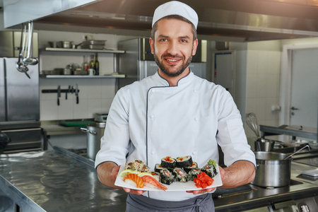 Already ready. Portrait of cheerful chef standing with cooked traditional japanese sushi