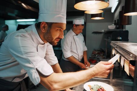 Chef cook checking the order at the restaurant kitchen