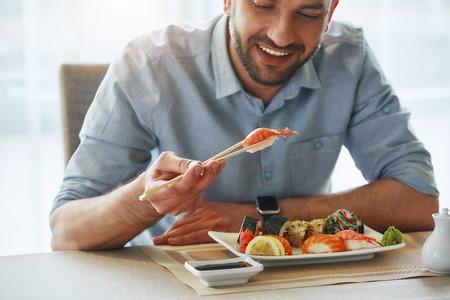 Better food, better mood. Cropped image of smiling handsome businessman eating sushi Stok Fotoğraf