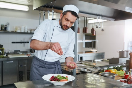 Chase the flavors. Ð¡ook preparing dish for serving. Modern commercial kitchen Stock Photo