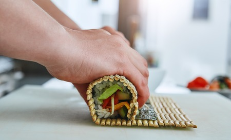 How to prepare sushi? Sushi master turns sushi rolls Stock Photo - 120919376