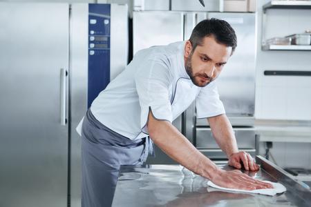 Cuando prepare alimentos manténgalo limpio, no se debe ver un área sucia. Macho joven cocinero profesional limpieza en cocina comercial