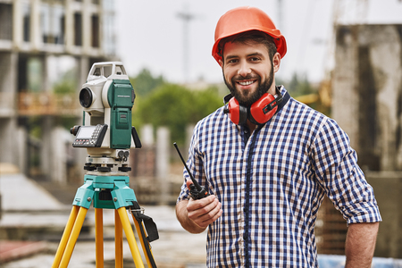 Surveyor equipment. Surveyor engineer in protective wear and red helmet using geodetic equipment, holding walkie talkie and smiling while standing at construction site