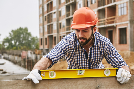 Accuracy and quality. Construction worker in protective yellow helmet checking the level of a plank of wood. Measurement concept