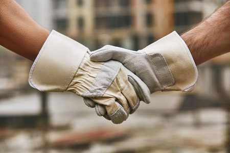 Good job! Close up photo of builders in protective gloves shaking hands against blurred construction site. Team work.