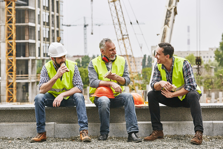 Time for a break. Group of builders in working uniform are eating sandwiches and talking while sitting on stone surface against construction site. Building concept. Lunch concept Stock Photo