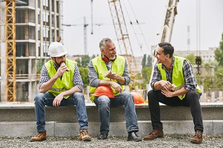 Zeit für eine Pause. Eine Gruppe von Bauarbeitern in Arbeitsuniform isst Sandwiches und spricht, während sie auf einer Steinoberfläche gegen die Baustelle sitzt. Gebäudekonzept. Mittagskonzept