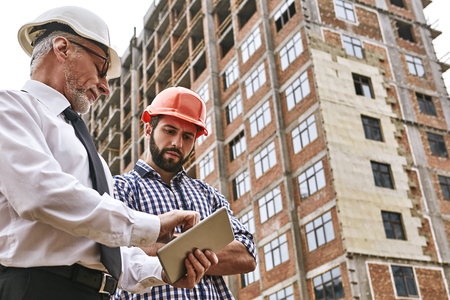 Discussion of the work plan. Senior professional engineer in formal wear and white helmet is showing project plan on digital tablet to young builder while standing at construction site. Stock Photo