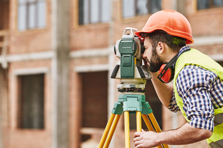 Geodetic works. Surveyor engineer in protective wear and red helmet using geodetic equipment at construction site. Professional equipment. Stock Photo - 120919227