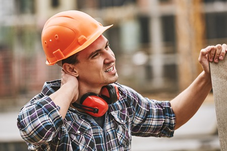 Be careful. Construction worker in protective helmet feeling neck pain while working at construction site. Pain concept. Dangerous job 스톡 콘텐츠 - 120919231
