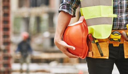 Construction worker. Cropped photo of male professional builder in working uniform with construction tools holding a safety red helmet while standing outdoor of construction site Standard-Bild