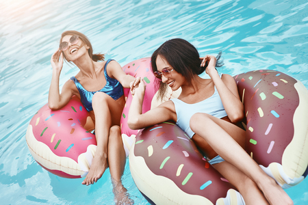Life is cool in the pool. Girls relaxing with inflatable rings in the shape of donuts