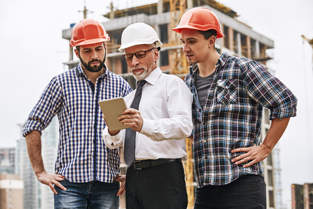 Using modern technologies. Senior engineer is looking at project plan on digital tablet with two young builders while working at construction site