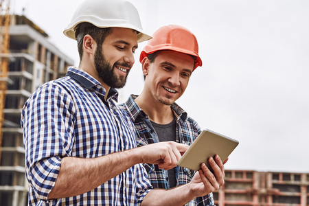 Working in team. Two young and cheerful builders in protective helmets are using digital tablet and working while standing at construction site