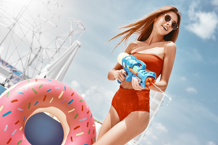 Summer is...bikinis, towels, soaking up the sun, oceans, beaches, just having fun. Young woman shooting with water gun in sunny day