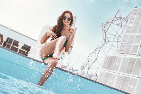 Summer Splash! Portrait of slim fashion model in green swimsuit having fun near the pool Standard-Bild