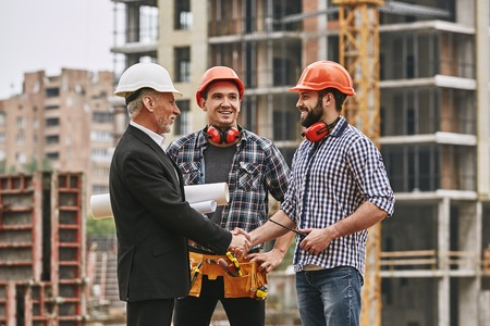 Good job! Cheerful elderly engineer in formal wear and white helmet holding engineering drawings and shaking hands of two happy young builders while standing at construction site.