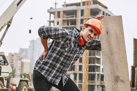 Hard work. Construction worker in protective helmet feeling back pain while working at construction site. Building construction. Pain concept Standard-Bild
