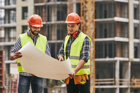 Look here! Two young builders in working uniform and helmets are holding a construction drawing in their hands and discussing it with each other while standing at construction site.