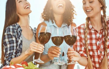 ¡Salud! Tres mujeres jóvenes y felices sosteniendo vasos con vino y riendo mientras están de pie en el techo. Concepto de barbacoa. Concepto de verano. Amistad Foto de archivo