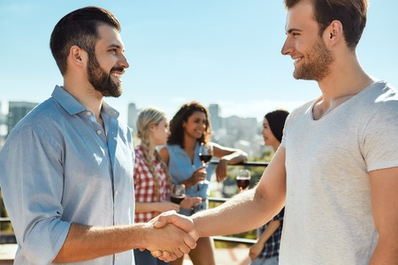 Nice to meet you! Two happy young men shaking hands and smiling while standing on the roof with friends. Barbecue concept. Summer concept Foto de archivo - 126117194