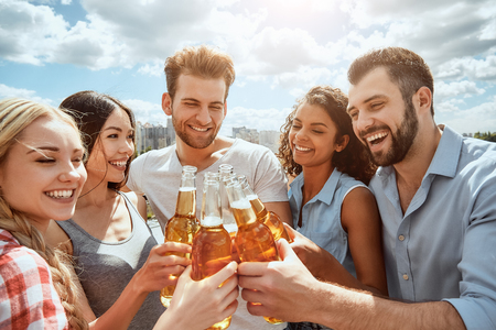Cheers to friends! Group of happy young people are clinking bottles with beer and smiling while standing on the roof. Barbecue concept. Summer time