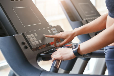 Starting to run. Close up photo of woman in sportswear pushing a start button on treadmill at gym. Cardio workout