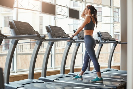I can not run anymore. Full length of young women in sports clothing keeping hand on forehead and feeling tired while running on a treadmill at gym.