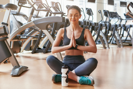 Meditating at gym. Beautiful young woman in sports clothing holding hands clasped and keeping eyes closed while sitting at lotus position. Yoga concept. Sport concept
