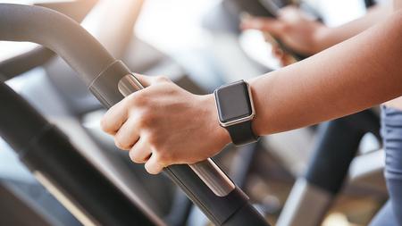 Tecnologie intelligenti. Foto ravvicinata dell'orologio intelligente sulla mano della donna che tiene la maniglia della macchina cardio in palestra. Concetto di fitness e sport. Archivio Fotografico