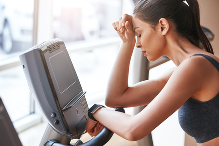 Feeling tired. Side view of young woman in sports clothing keeping hand on forehead while exercising at gym