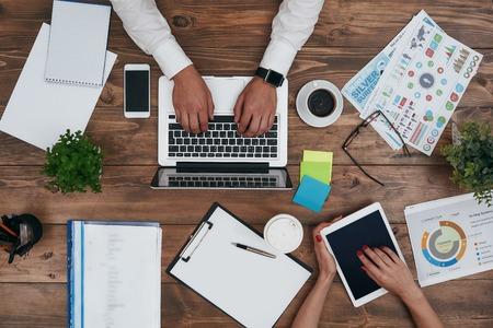 Vista superior del hombre y la mujer trabajando, usando laptop y tabletc pc. Ordenador portátil, planta en maceta, diario, taza de café, vasos, gráficos y otros suministros en el escritorio de madera marrón. Compañeros que trabajan en la oficina. Tiro horizontal