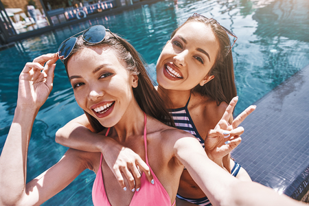 Say cheese! Joyful and cute young women in swimwear making selfie and smiling while standing against pool outdoors.