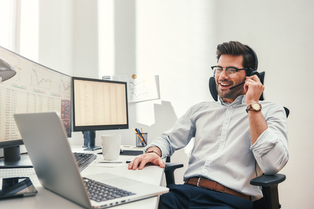Buenas noticias. Feliz comerciante barbudo joven en auriculares hablando con el cliente y sonriendo mientras está sentado en su oficina moderna. Concepto de negocio. Concepto de comercio. Concepto de comunicación
