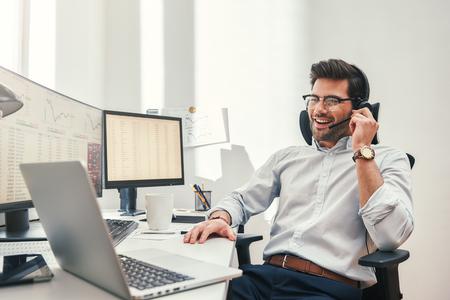 Goed nieuws. Gelukkige jonge bebaarde handelaar in headset die met de klant praat en glimlacht terwijl hij in zijn moderne kantoor zit. Bedrijfsconcept. Handelsconcept. Communicatie concept