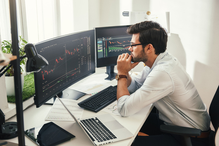 Successful trader. Back view of bearded stock market broker in eyeglasses analyzing data and graphs on multiple computer screens while sitting in modern office. Stock exchange. Trade concept. Investment concept Archivio Fotografico