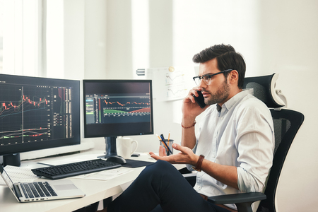 Really? Worried bearded businessman or trader in formalwear and eyeglasses is talking with client and gesturing while sitting in modern office. Trade concept. Investment concept. Modern technologies Imagens