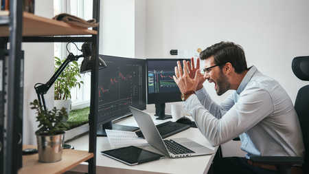 Failing! Frustrated young businessman or trader in formalwear is shouting and feeling angry while looking at trading charts and financial data in the office. Stock exchange. Financial trading concept. Investment concept
