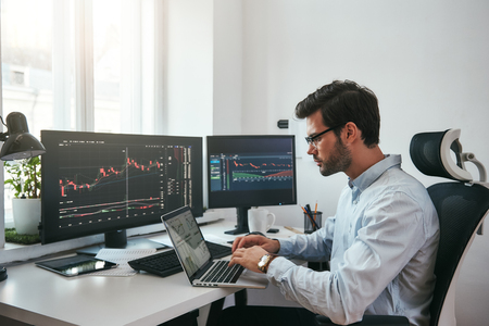 Workplace of trader. Young bearded trader wearing eyeglasses using his laptop while sitting in office in front of computer screens with trading charts and financial data. Stock exchange. Financial trading concept. Investment concept