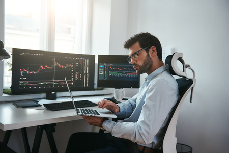 Business Information. Bearded trader wearing eyeglasses analyzing financial market via laptop while sitting in office in front of computer screens with trading charts. Stock exchange. Trade concept. Investment concept 写真素材