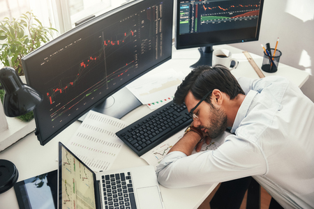 I need to relax. Tired young bearded trader in formal wear sleeping on the desk while working late in his modern office. Trade concept. Investment concept. Rest concept Imagens