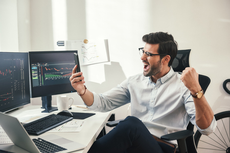 Great! Excited young trader or businessman in formalwear and eyeglasses shouting and gesturing in office while looking at trading charts on his smartphone. Forex market. Trade concept. Investment concept