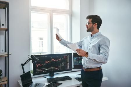 Handelsstrategie. Intelligenter und junger Händler in Brillen, der Finanzberichte betrachtet und Handelsdiagramme analysiert, während er in einem modernen Büro vor Computerbildschirmen steht. Börsenmakler. Forex-Markt. Handelskonzept Standard-Bild