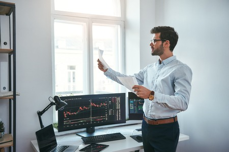 Trading strategy. Smart and young trader in eyeglasses looking at financial reports and analyzing trading charts while standing in front of computer screens in modern office. Stock broker. Forex market. Trade concept