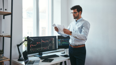 Analyzing data. Thoughtful trader in eyeglasses holding a financial report and analyzing trading charts while standing in front of computer screens in modern office. Stock broker. Forex market. Trade concept
