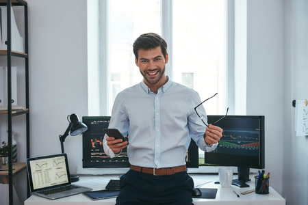 Great! Happy young businessman or trader in formalwear holding eyeglasses and smartphone and smiling while standing in front of computer screens with trading charts in the office. Forex market. Business concept. Investment concept Stock Photo