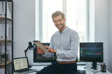 Business success. Cheerful young trader in formal wear is holding digital tablet and looking at camera with smile while standing in front of computer screens with trading charts in the office. Forex m 写真素材