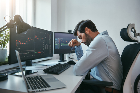 Time to take a break. Side view of tired young businessman or trader holding eyeglasses and feeling tired while working with data and charts on computers at his modern office. Forex market. Trade concept. Business concept