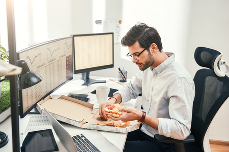 I love pizza! Young bearded businessman or trader in eyewear and formal clothes is eating hot pizza while sitting in his modern office. Coffee break. Food concept. Business concept. Trade concept