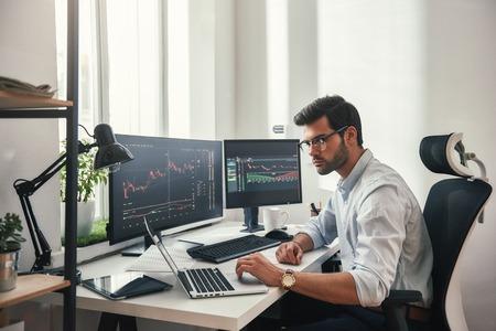 Drukke werkdag. Jonge, bebaarde handelaar in brillen die met laptop werkt terwijl hij in zijn moderne kantoor voor computerschermen met handelsgrafieken zit.
